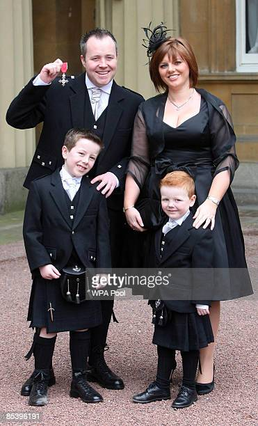Snooker player John Higgins attends an investiture at Buckingham Palace after receiving an MBE from the Princess Royal with his wife Denise and two...