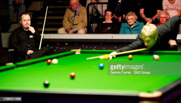 John HIGGINS v Neil ROBERTSON .RAVENSCRAIG - MOTHERWELL.John Higgins takes a seat while his opponent Neil Robertson finds his way around the table