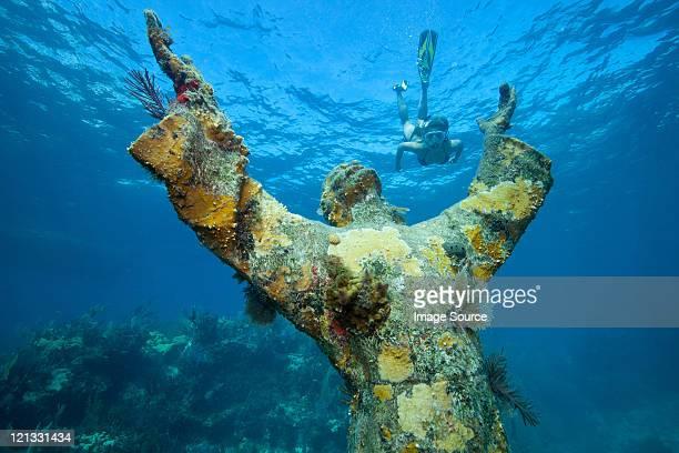 Snorkeler and underwater statue