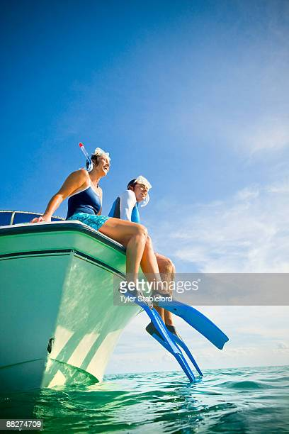 Snorkelers on the side of a boat.