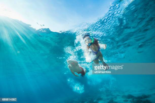 Snorkeling adventure. Best friends. Young man and woman, diving into the sea. Underwater turquoise lagoon. Happy teenage couple swimming, joy into the crystal clear sea. Mediterranean beach. Summer sea romance.