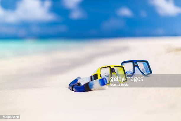 Snorkeling mask and snorkel on sand beach near the water