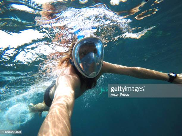 snorkeling near a tropical island. young man swims in the water. - scuba mask stock pictures, royalty-free photos & images