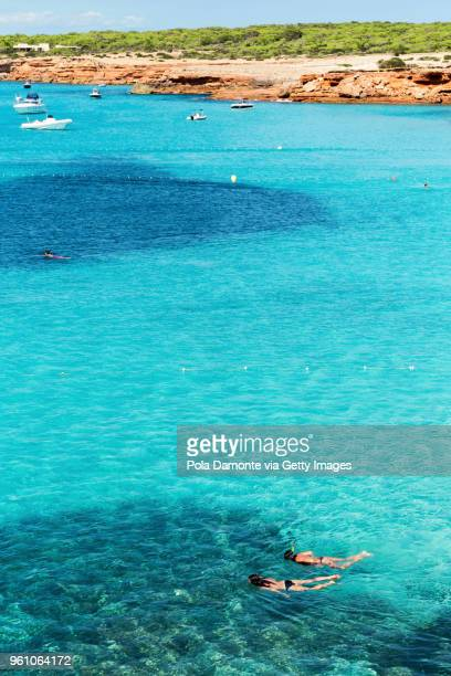 Snorkeling or scuba diving at emerald idyllic beach of Cala Saona from high view angle, Formentera coastline in Balearic Islands, Spain