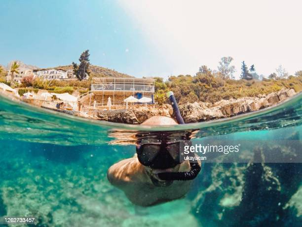 snorkeling young man in turquoise sea - kas stock pictures, royalty-free photos & images