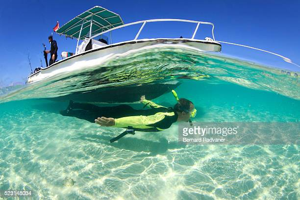 snorkeller diving down a boat