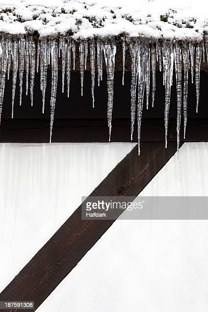 Snow and a row of icicles hanging from the eaves of a building