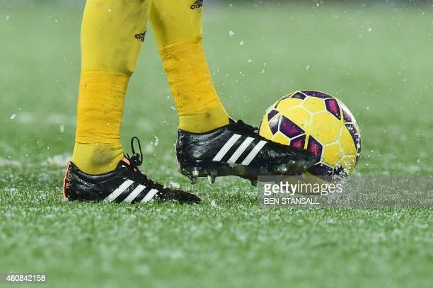 Snow and ice are seen as West Bromwich Albion's English goalkeeper Ben Foster controls the ball during the English Premier League football match...
