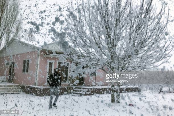 Snow and ice coat a window as a man walks by a snow covered tree in Van Turkey on December 07 2017