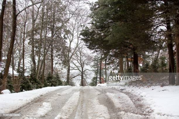 Snow and ice covers a road during a winter storm that brought snow sleet and rain to the area on January 20 2019 in Hingham Massachusetts Icy...