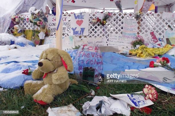 A snow and rain soaked stuffed bear sits next to a burning candle at a makeshift memorial in a park 23 April 1999 next to Columbine High School in...