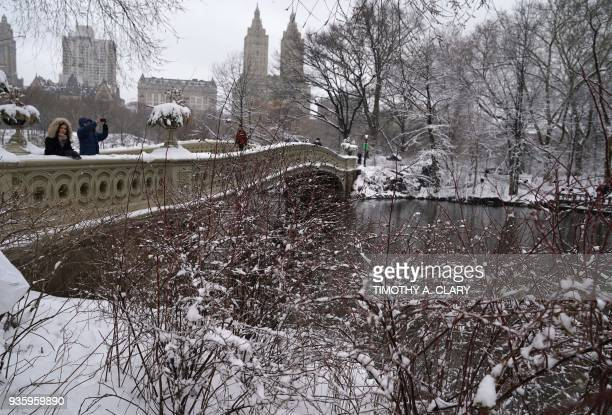 Snow around the Bow Bridge in Central Park in New York March 21 2018 as the fourth nor'easter in a month hits the tristate area on the first full day...