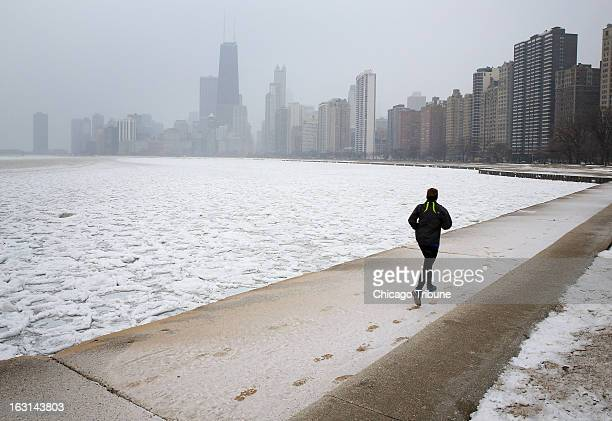 Snow begins to stick as morning runners take to the lakefront path early morning in Chicago Tuesday March 5 2013