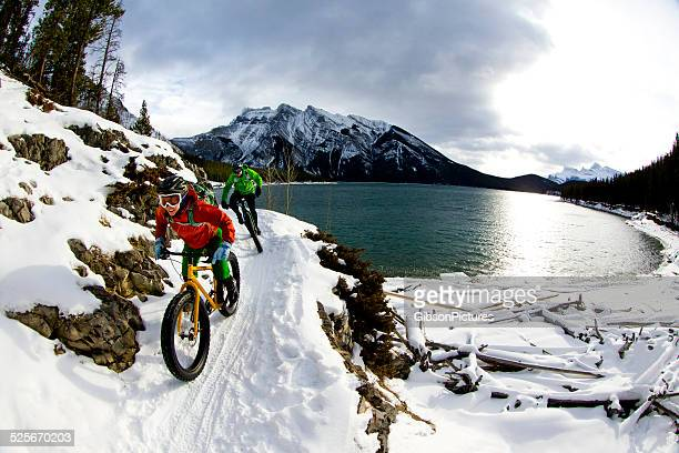 snow biking couple - avontuur stockfoto's en -beelden