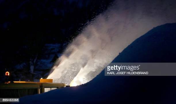 A snow blower clears a parking site from snow in Oberjoch southern Germany before sunrise on December 29 2017 / AFP PHOTO / dpa / KarlJosef...