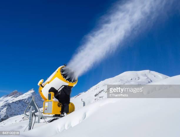 snow cannon (snow gun) is spraying artificial snow onto ski slope
