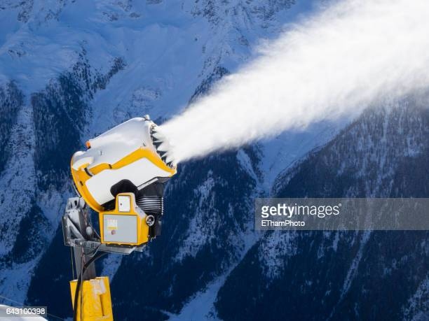 snow cannon (snow gun) is spraying artificial snow onto ski slope