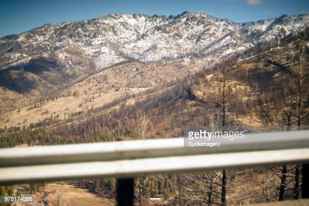 Snow capped mountains behind guard rail