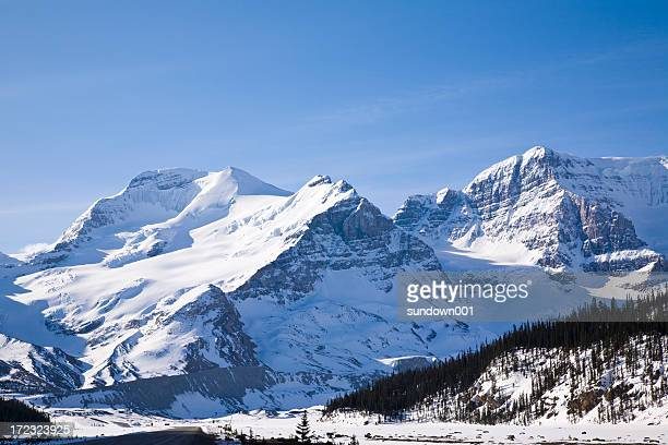 snow capped mountains with a blue sunny day - rocky mountains stock pictures, royalty-free photos & images