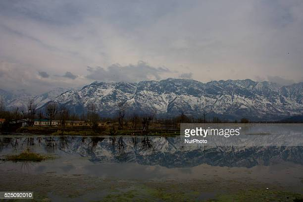 Snow capped Zabaran mountains are reflected on the Dal Lake on March 19 2015 in Srinagar the summer capital of Indianadministered Kashmir India Known...