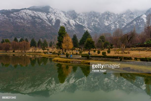 Snow clad mountain range is reflected on a pond during a cold day on December 15 2017 in Srinagar the summer capitol of Indian Administered Kashmir...