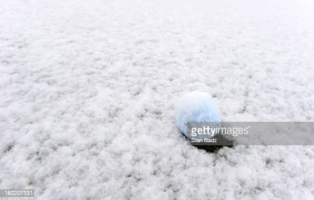 Snow continues to fall on a golf ball on the practice range as snow and rain caused play to be suspended due to weather during the first round of the...