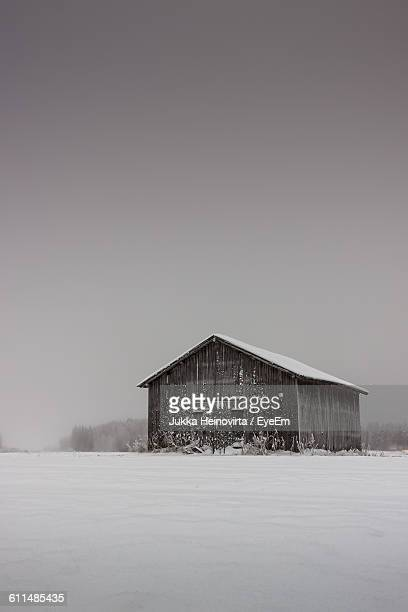 snow covered barn by field against clear sky - heinovirta stock pictures, royalty-free photos & images
