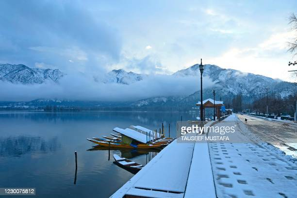 Snow covered boats are seen moored in Dal Lake after a fresh snowfall in Srinagar on December 12, 2020.