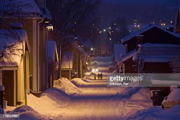 snow covered buildings and street at dawn - diepe sneeuw stockfoto's en -beelden