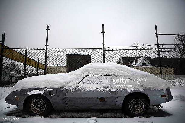 A snow covered car sits along a road on February 18 2014 in Brooklyn borough of New York City After a harsh winter of record snow fall in much of New...
