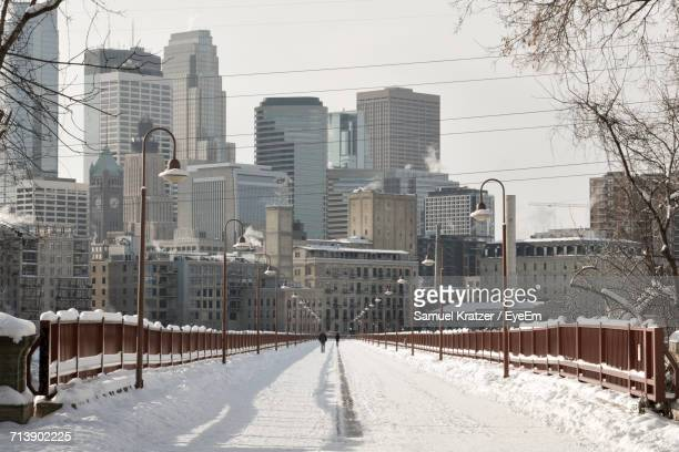 snow covered city against sky - minneapolis stock photos and pictures