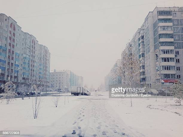 Snow Covered City Street Amidst Buildings Against Sky