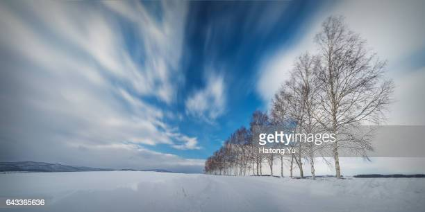 Snow covered country road with long exposure clouds in Hokkaido, Japan