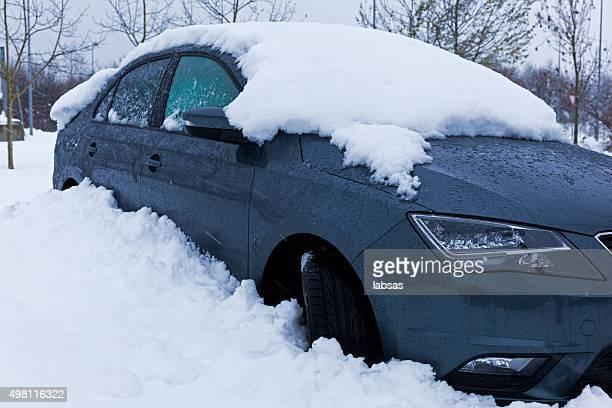 Nieve cubierta gris oscuro que estacione en el estacionamiento de automóviles.