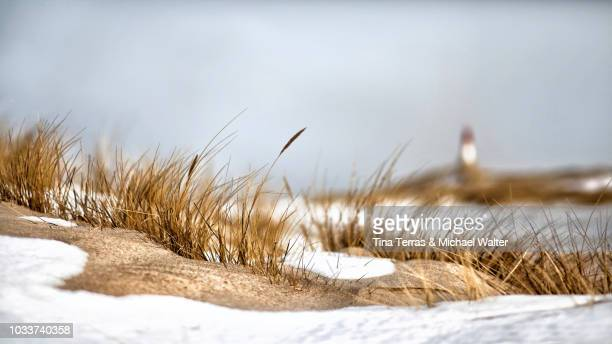 Snow covered dunes with lighthouse on the Isle of Sylt in winter