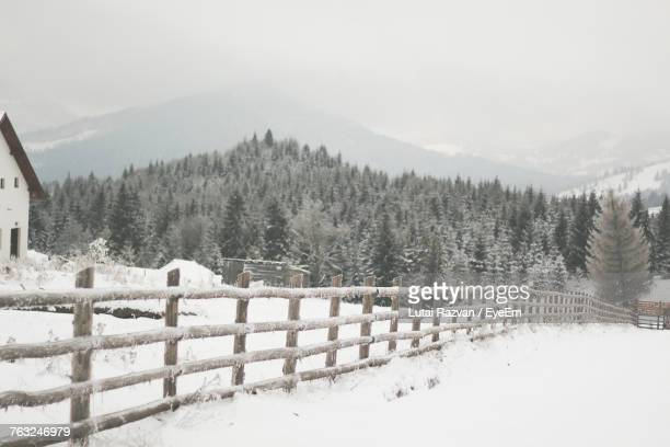 snow covered fence on landscape against sky - lutai razvan stock pictures, royalty-free photos & images