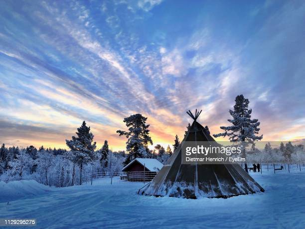 snow covered field against sky during sunset - swedish lapland stock photos and pictures