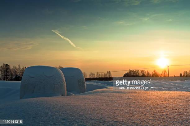 snow covered field against sky during sunset - heinovirta stock photos and pictures