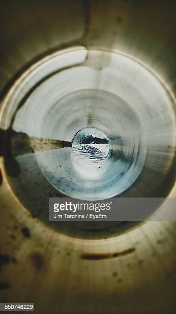 Snow Covered Field Seen Through Pipe