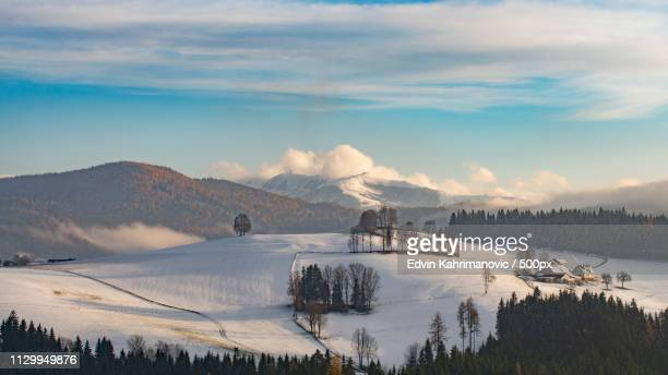 snow covered fields on hill with mountain range on horizon - hill range stock pictures, royalty-free photos & images