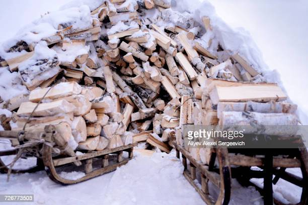 Snow covered firewood on wooden sleds