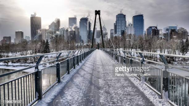 snow covered footbridge amidst buildings in city - calgary stock pictures, royalty-free photos & images