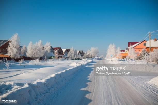 snow covered houses against clear blue sky - deep snow stock pictures, royalty-free photos & images