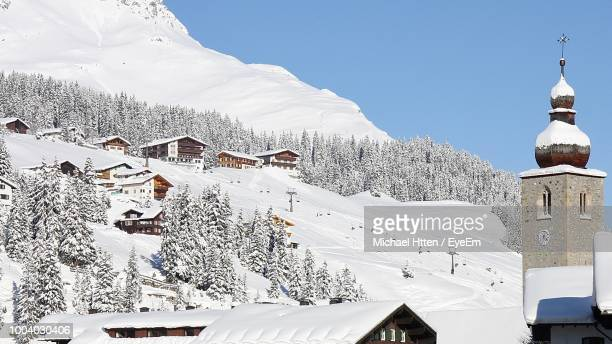 snow covered houses and trees during winter - lech stock photos and pictures