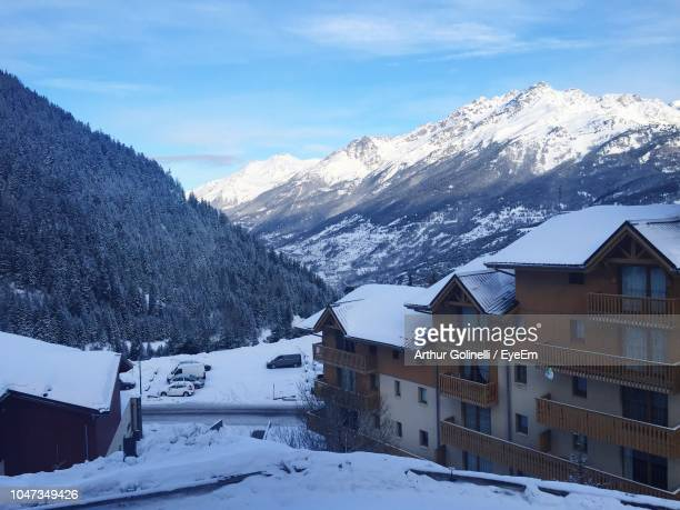 snow covered houses by buildings against sky during winter - arthur foto e immagini stock