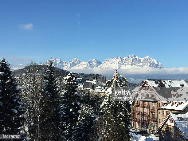 snow covered houses in town - kitzbuehel stock-fotos und bilder