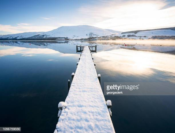 snow covered jetty on loch earn in scotland - scotland stock pictures, royalty-free photos & images