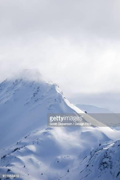 snow covered kenai mountain peaks under clouds, kachemak bay state park - kenai mountains stock pictures, royalty-free photos & images