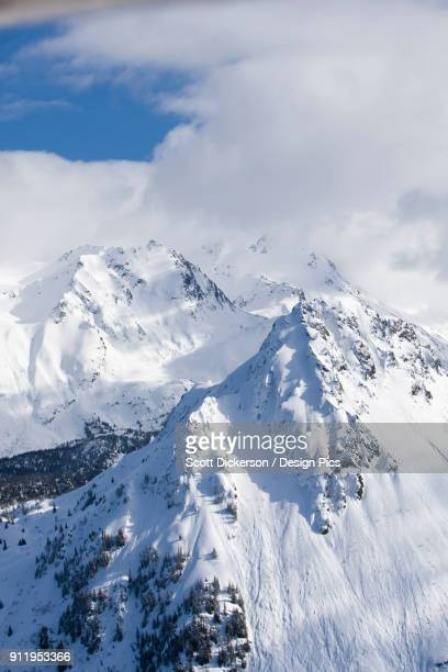 snow covered kenai mountains with blue sky peaking out from the clouds, kachemak bay state park - kenai mountains stock pictures, royalty-free photos & images