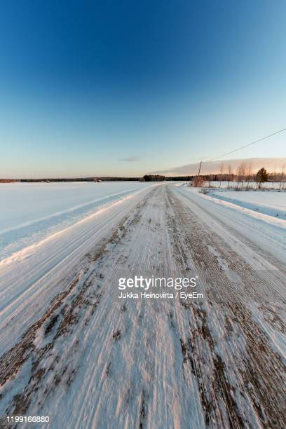 snow covered land against clear blue sky - heinovirta stock photos and pictures